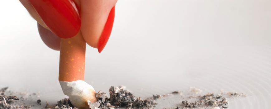 Dedos de mujer apagando un cigarro
