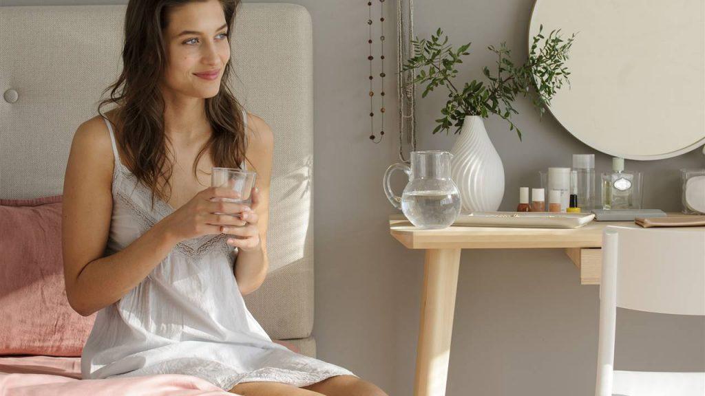 Chica en cama a punto de tomar agua en ayunas
