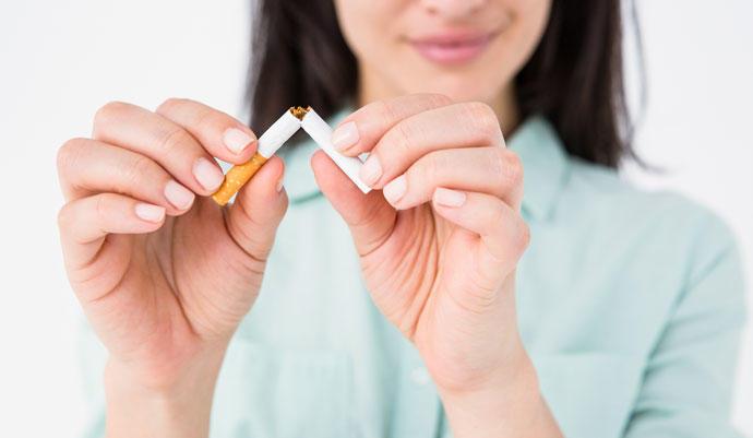 Chica rompiendo un cigarro en dos