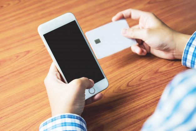 Chico con celular y tarjeta en mano