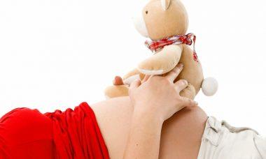 Chica embarazada con peluche encima