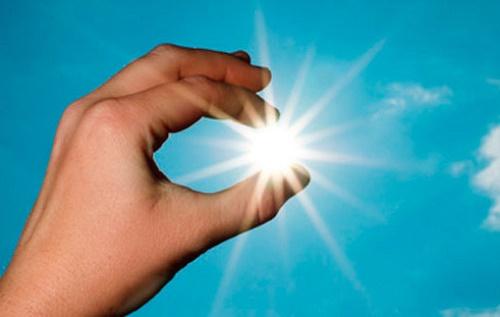 Mano sobre la silueta del sol