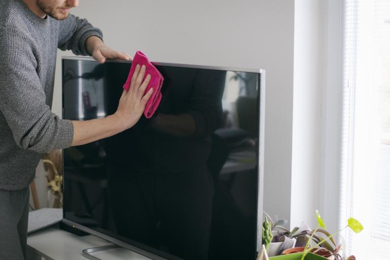 Hombre limpiando su tv