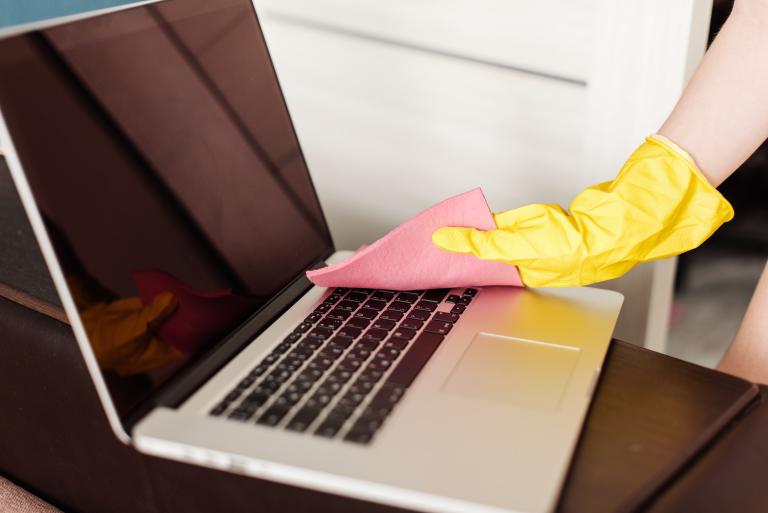Mujer limpiando laptop